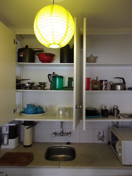 Kitchen cupboards equipped to cook meals.