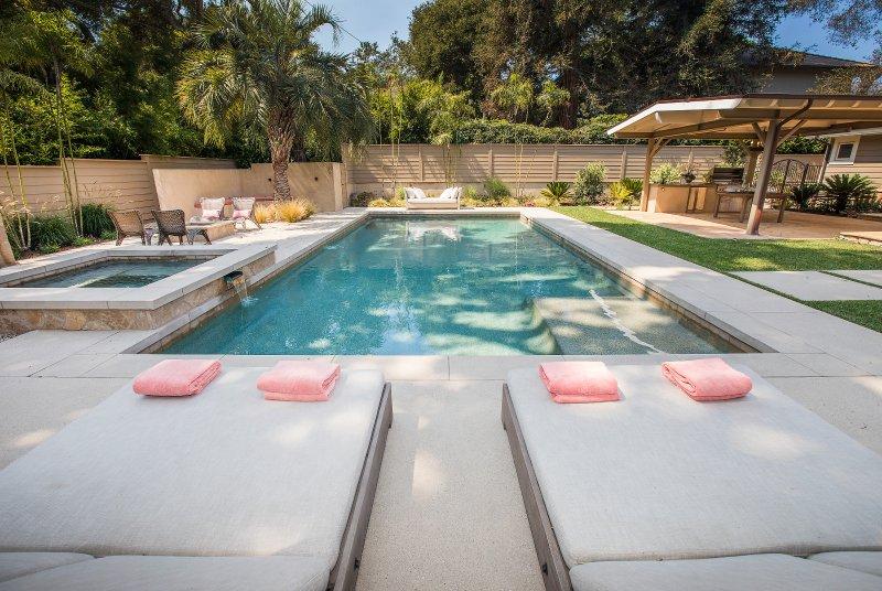 Rilassarsi sulle sedie a sdraio di fronte alla piscina