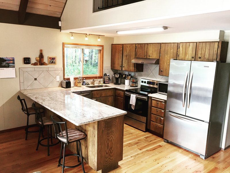 Modern kitchen with breakfast bar and stainless steel appliances.