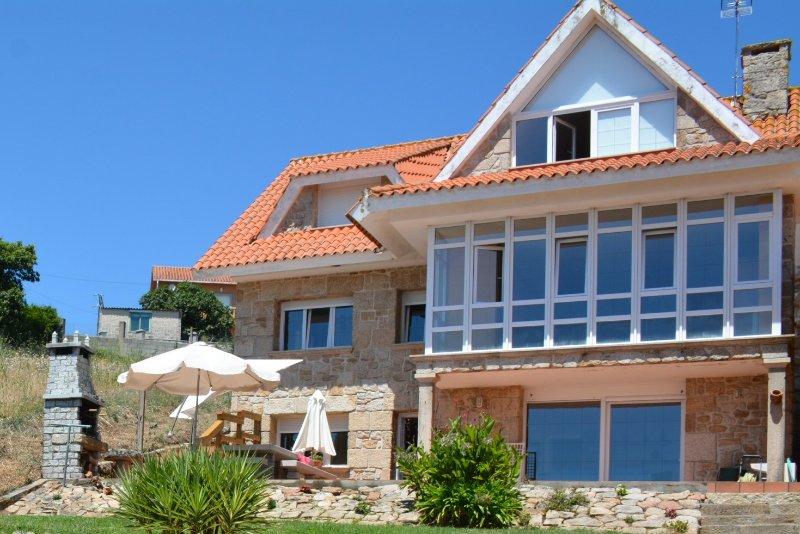Casa mirando al mar a 50 metros de la playa, aluguéis de temporada em Ribeira