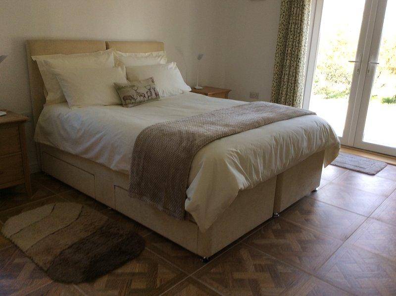 Chambre n ° 1 avec lit king size et salle d'eau privative. Portes patio vers la zone privée.