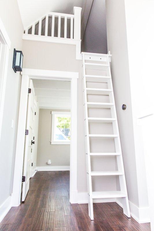 Vista del pasillo de arriba w / escalera al desván. Será abastecido con juegos y juguetes