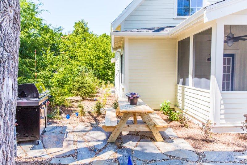 patio trasero de losas w / parrilla de gas, mesa de picnic y entorno privado