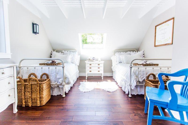 dormitorio con dos camas en el segundo nivel. Armario repleto de ropa para bebé