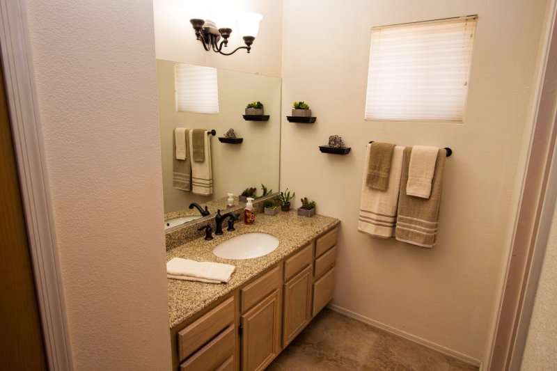 Master Bathroom with brand new granite sink top and accessories, custom tile flooring.