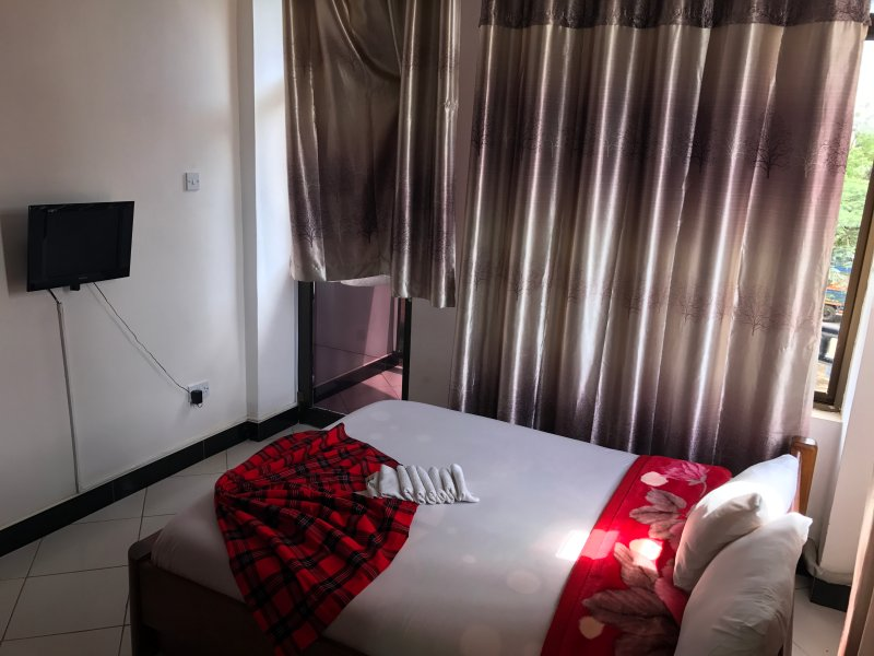 Double bed with city view decorated with Masai sheets/clothing.