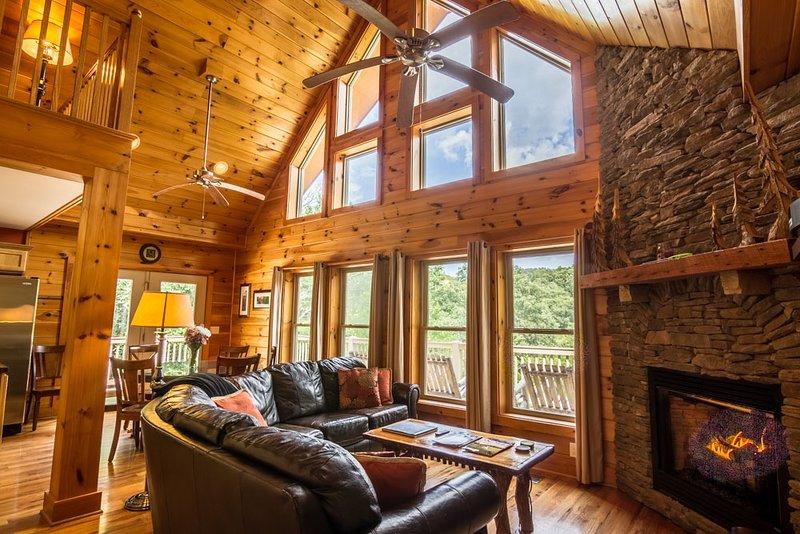 Soggiorno con finestre dal pavimento al soffitto, ampio divano e camino
