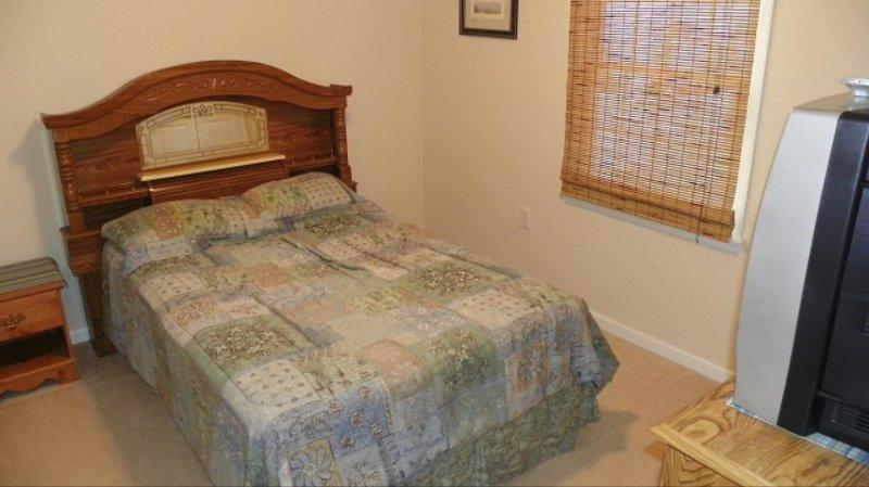 Dormitorio con cama de tamaño completo, frente a la sala de baño