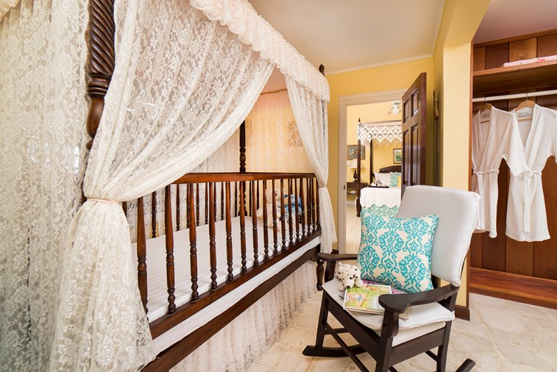...  adjoins a dressing room with a restored antique lace-trimmed spindle crib.