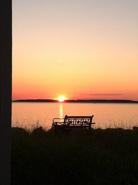 Cottage bench at sunset with Great Island.
