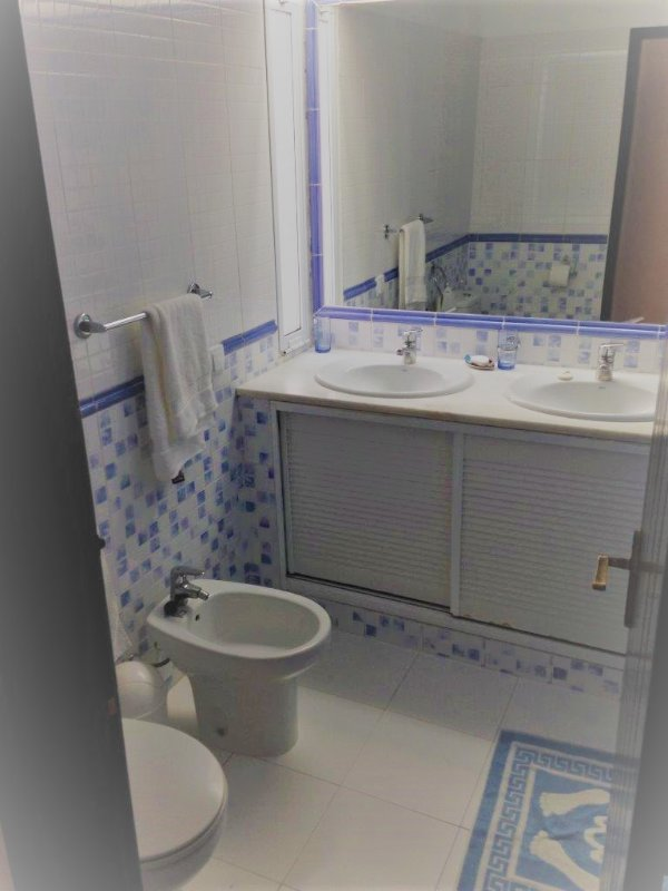 Bathroom with twin basins, toilet, bidet and bath with shower
