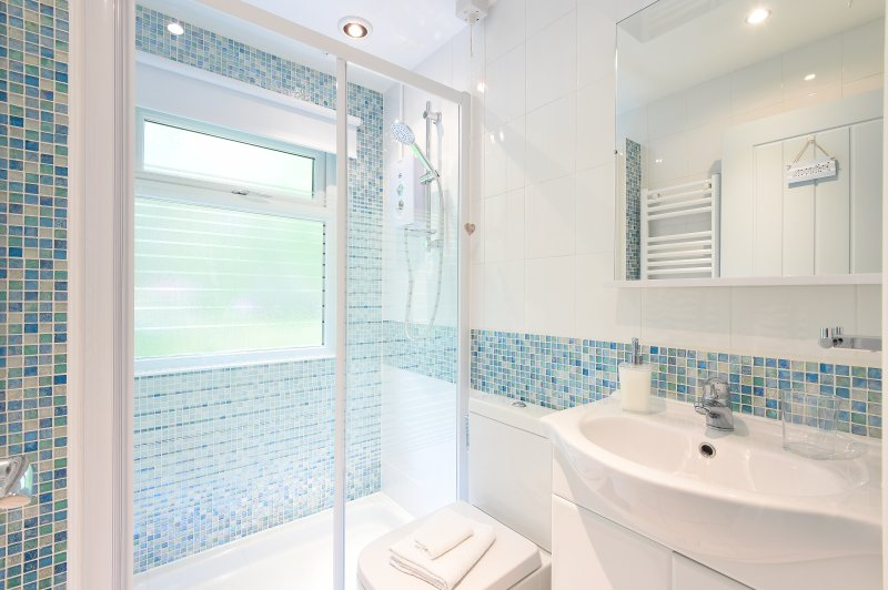 Spacious walk in shower room with towel radiator