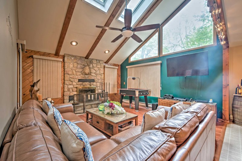 Lounge around in the living room with a large leather sectional, wood-burning fireplace, table hockey table, and flat-screen cable TV.