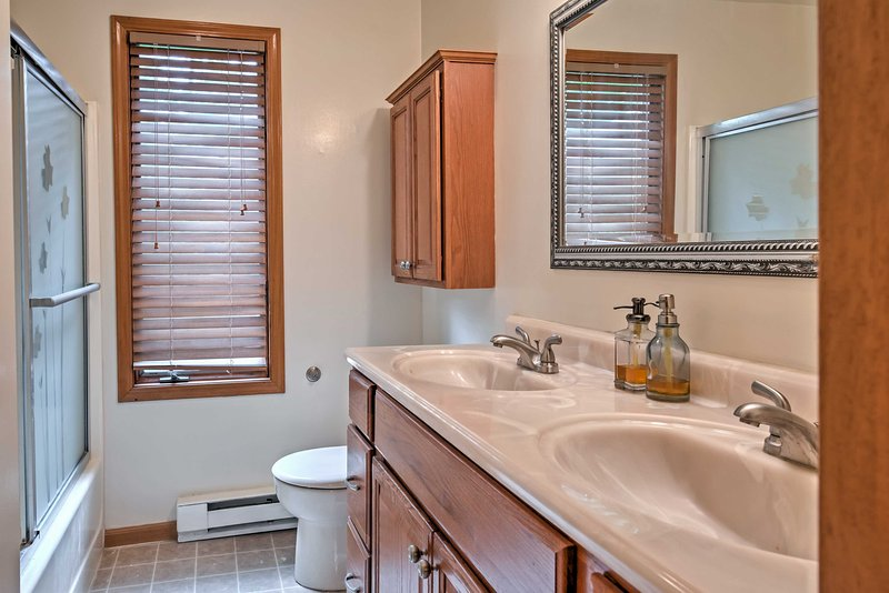The bathroom features his and hers sinks and a shower/tub combo.
