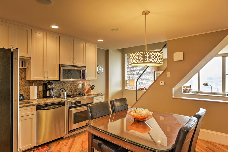 La cocina está equipada con electrodomésticos de acero inoxidable y un conjunto mesa de comedor para 4.