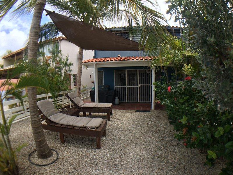 Nuestro patio trasero jardín tropical con palmeras y vela de la cortina.