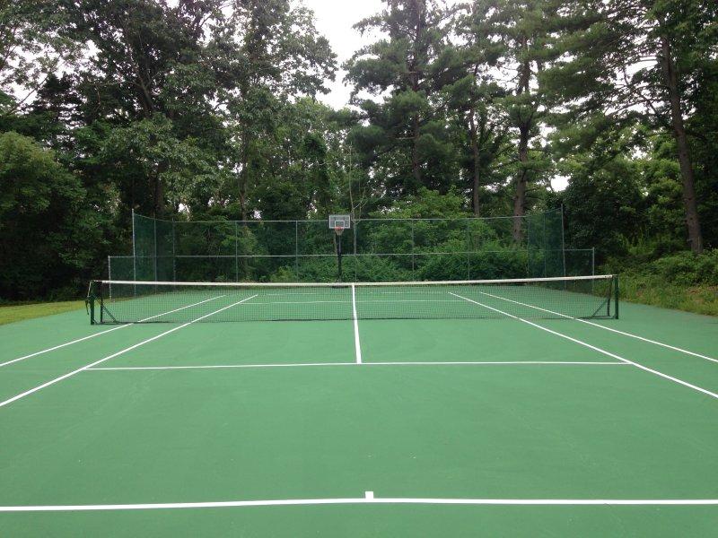 Campo de tenis con tablero de baloncesto