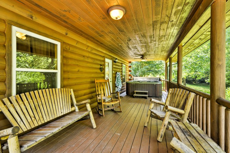 The rustic cabin features a deck with a hot tub and ample seating to lounge on.