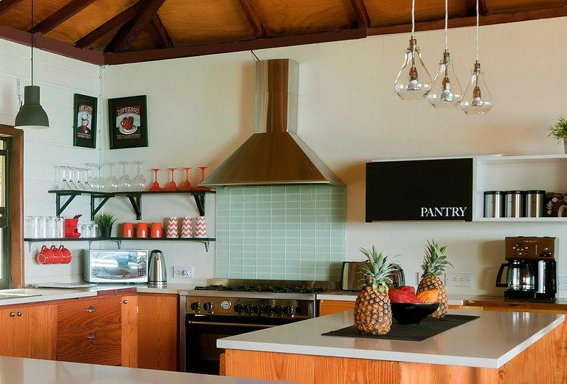 Modernt kök med en sex-brännare gasspis och många andra små apparater