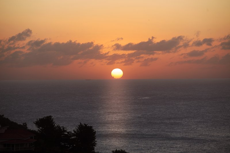 Från däck, njuta av den vackra solnedgången störtar i havet i rosa färger