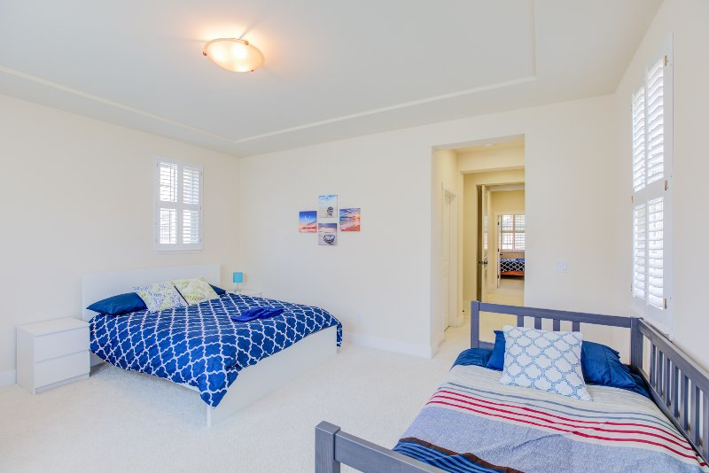This bedroom is furnished with a queen bed and a day bed. The room is pristine white with soft glow