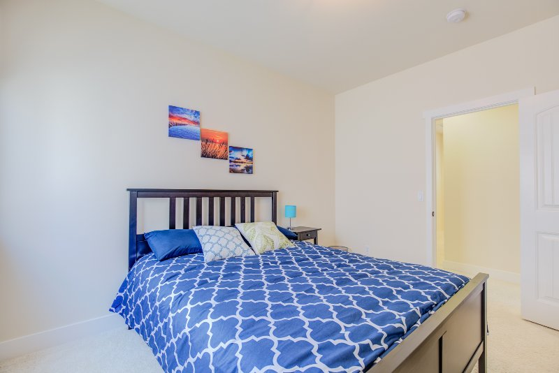 Main bedroom has a comfy queen bed, HD cable TV, sitting area which functions as a work space.