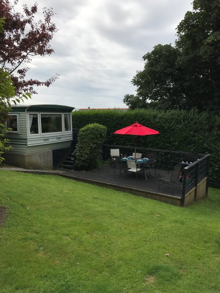 Plas Llwyd caravan set in private mature garden  with decking & garden furniture & A gas BBQ.