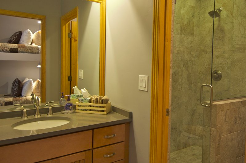 The bathroom has been recently remodeled & features tile wood and glass.