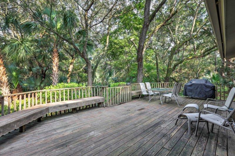 Ubicado en un entorno tropical, esta casa ofrece una gran cubierta trasera con vistas a las plantas de los bosques exuberantes.