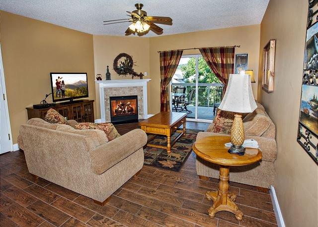 Living Room Has Hardwood floors with ceiling fan, flat screen t.