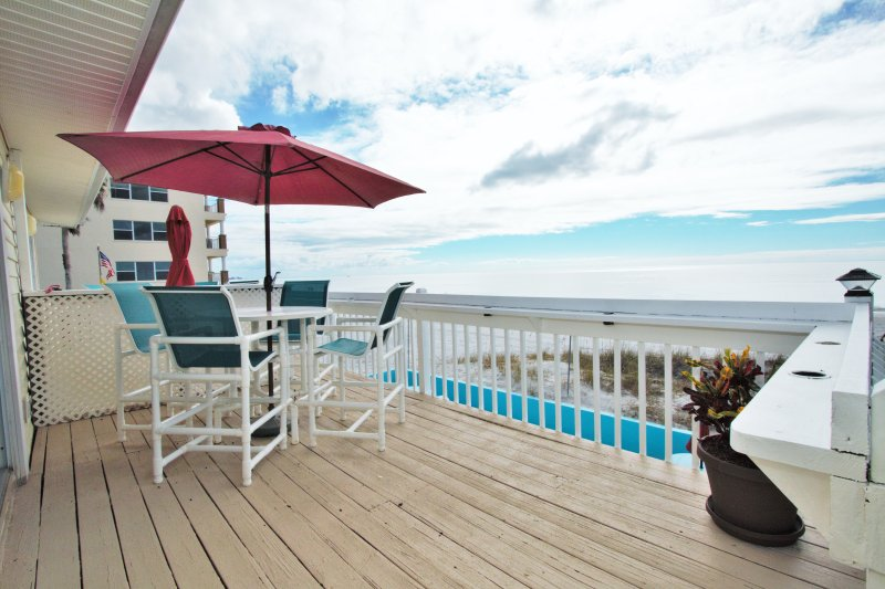 Beach facing deck with 4 top dining set. Amazing ocean views where you can enjoy meals, drinks and even dolphin watching.
