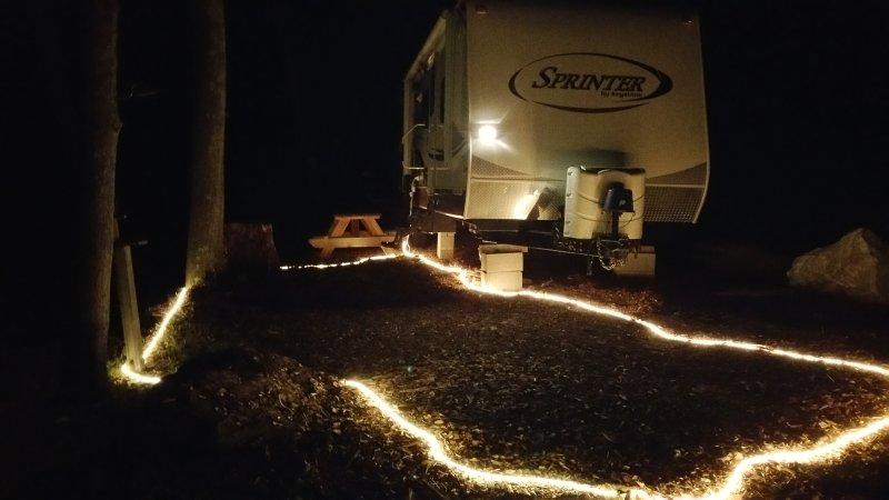 A luz área campista-se durante a noite com iluminação corda no chão