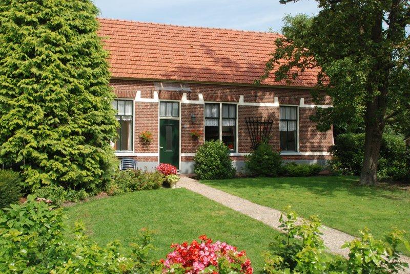 Vooraanzicht van De Ruiterskamp met de ruime tuin die tot aan de Berkel loopt
