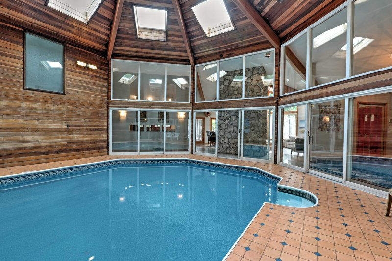 Ample sunlight fills the wood paneled interior of the indoor pool.