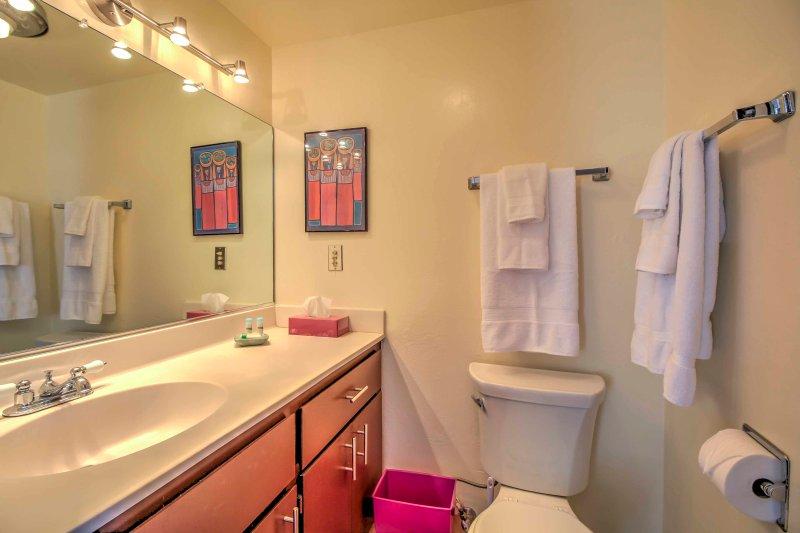 Baño # 1 tiene un solo lavabo y espejo grande.