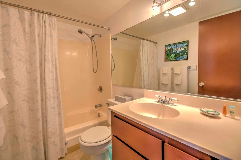 Baño # 2 tiene un fregadero de un seno, espejo grande, y una combinación de bañera / ducha.