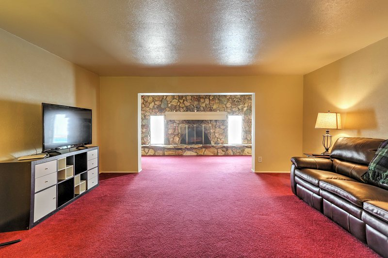 Relax in the living room, featuring a sumptuous leather sofa, flat-screen cable TV and a wood-burning fireplace.