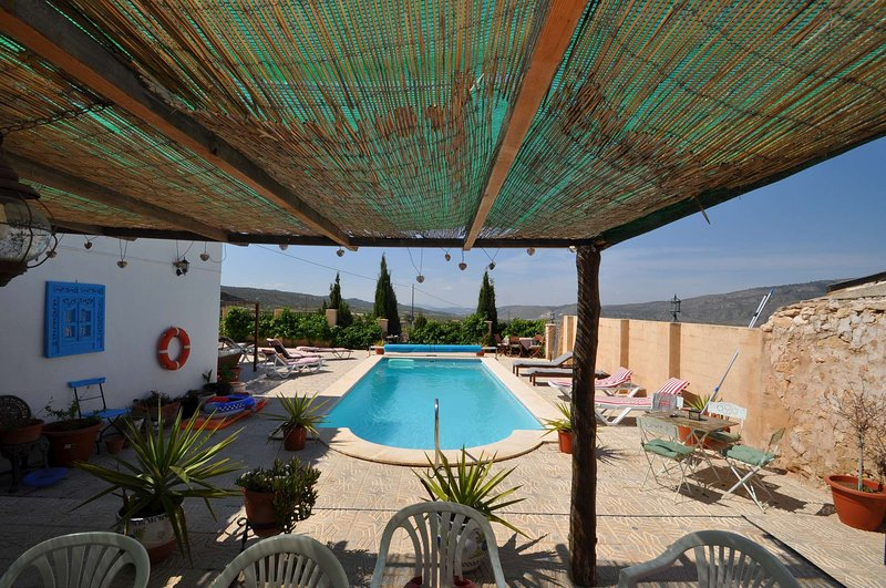 Casa Estrella's pool with dining and relaxation areas