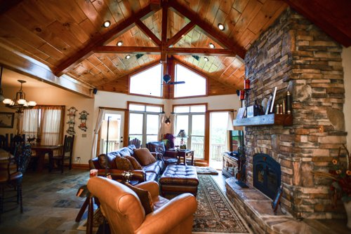 Upstairs living area, high end leather furnishings, fireplace, king trusses, slate flooring.