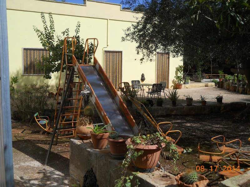 Statement of the house with garden and playground in the shade of olive trees.