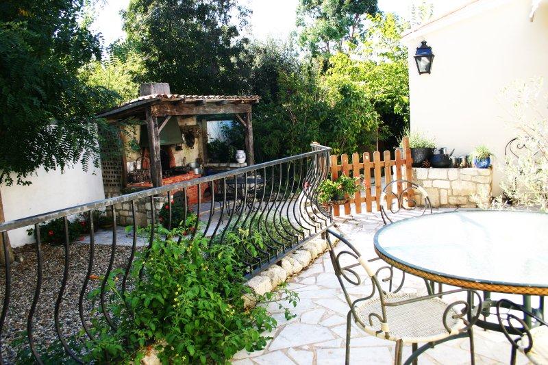 O terraço superior no jardim com a principal mesa e cadeiras e churrasqueira de alvenaria.