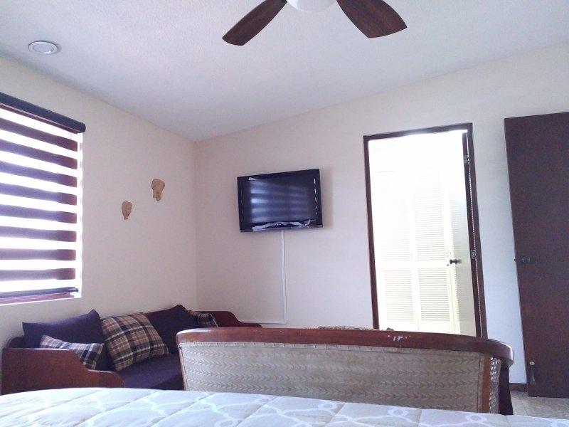Televisor de pantalla plana y un sofá grande, la habitación muy bien ventilado