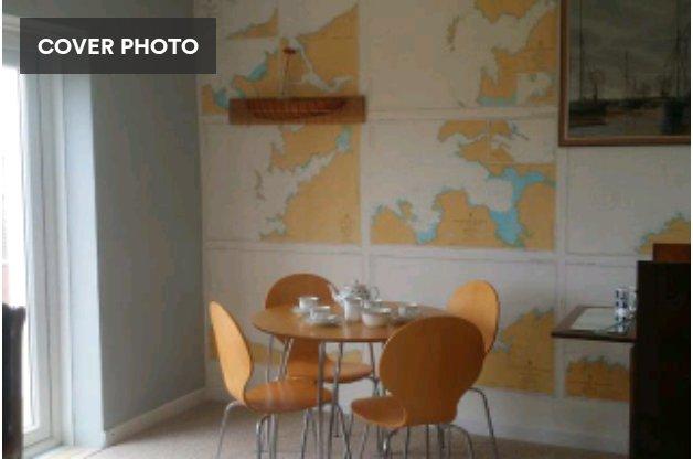 Salle à manger avec des portes donnant sur balcon et vue sur la mer, et coffret de cocktail rétro