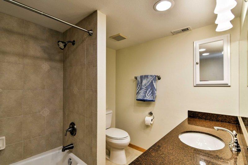 Cette salle de bains complète comprend un ensemble douche / baignoire et une coiffeuse en miroir.
