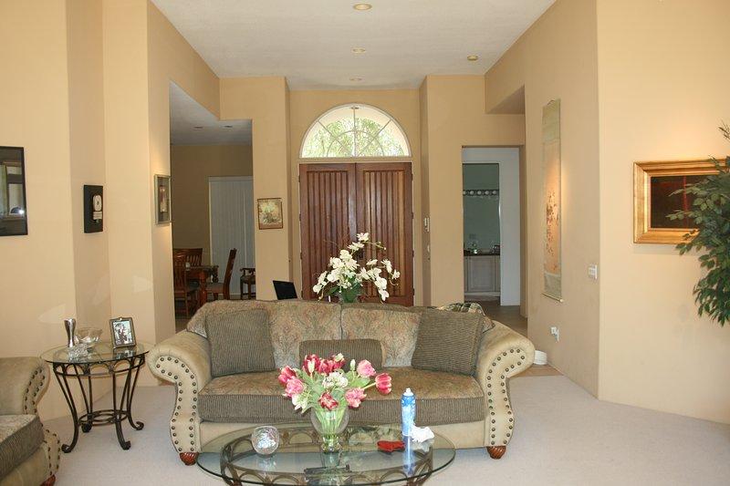 entrada frontal mirando hacia atrás desde la sala de estar formal; arte original, muebles finos