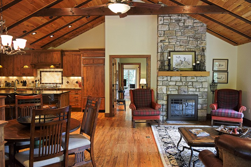Featuring a vaulted ceiling with exposed beams, the open floor plan of the home allows for a large living room area, where the unique two-sided stone fireplace is ready to light