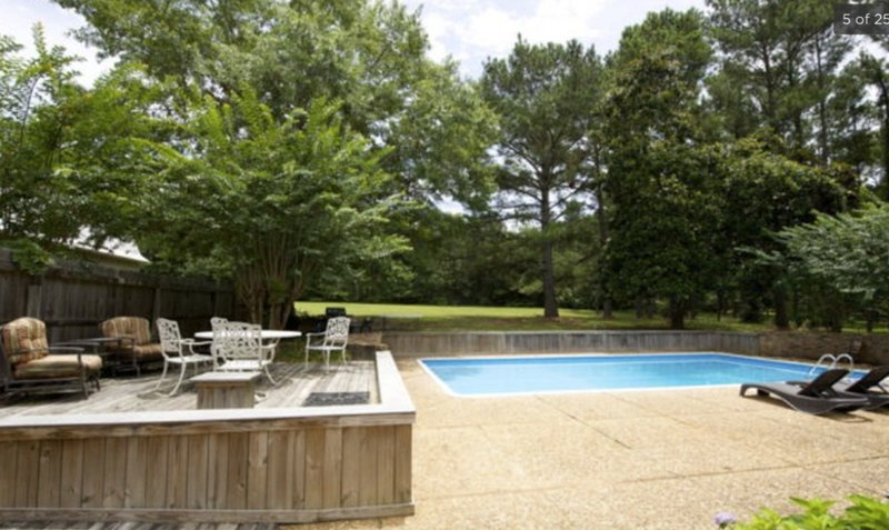 Large pool is surrounded by trees and grassy backyard.