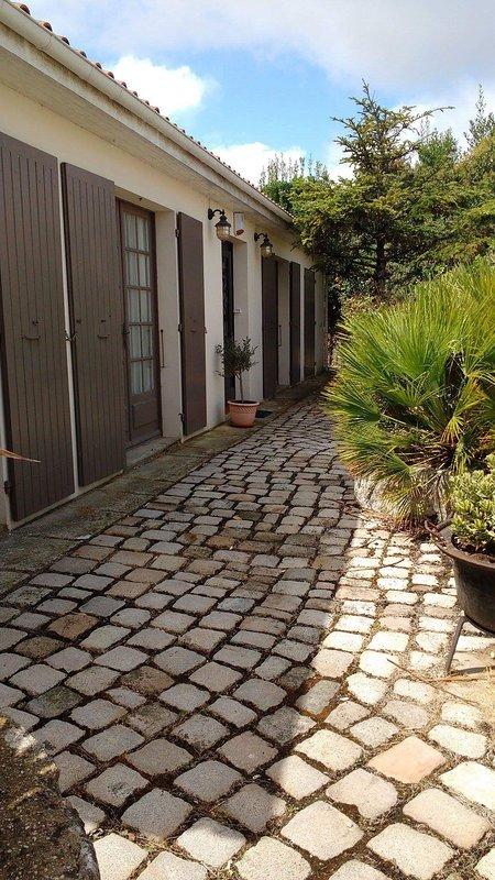 A frente da casa com suas pedras tradicionais de paralelepípedos e um poço antigo.
