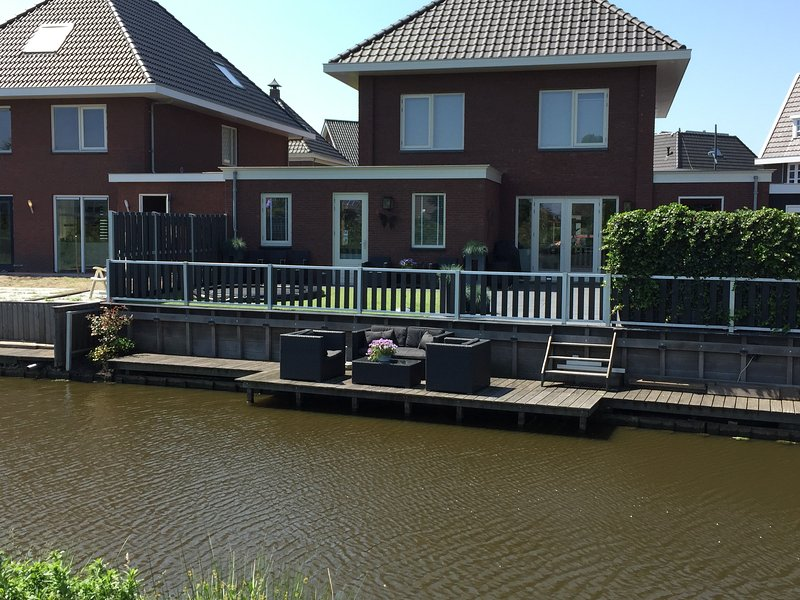 View to the back of the apartment at the water side with 2 areas to sit outside, dock and trampoline