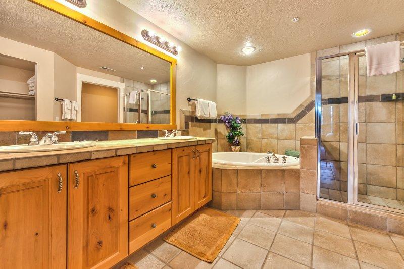 Master Bath 1 met dubbele wastafels, een Romeins bad en een stenen douche